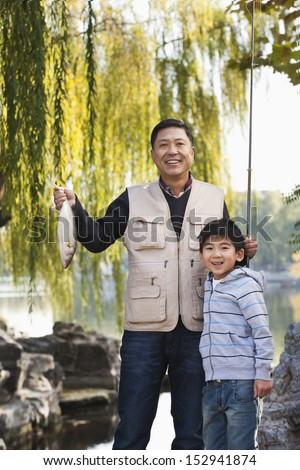 Father and son displaying fishing catch at lake - stock photo