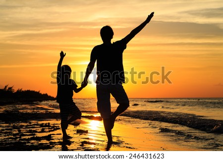 father and son doing yoga at sunset sea
