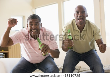 father and son drinking beer and cheering at television - stock photo