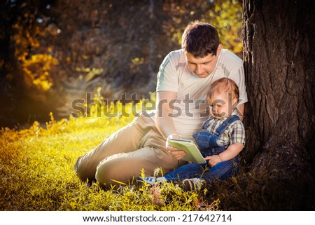 Father and son enjoy the summer in park. Outdoors. - stock photo