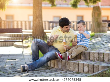 Father and son enjoying icecream outside in a park - stock photo
