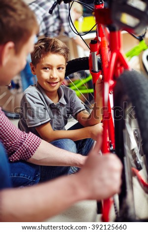 Father and son examining a bicycle together - stock photo