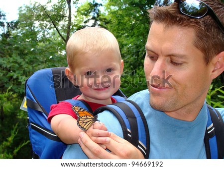 Father and son exploring nature - boy smiling with a butterfly on his hand