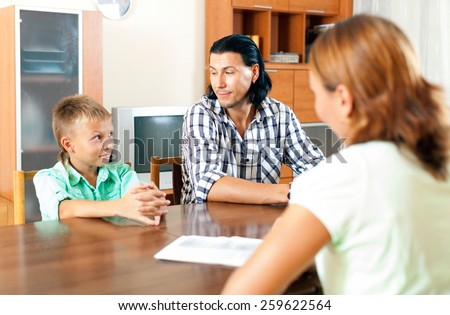 Father and son filling questionnaire for employee of the bank - stock photo