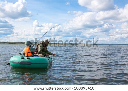 Father and son fishing at boat - stock photo