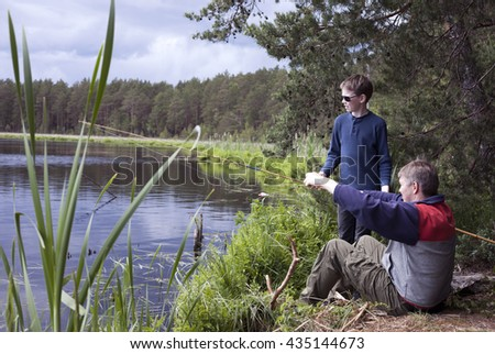 Father and son fishing at lake shore at spring day