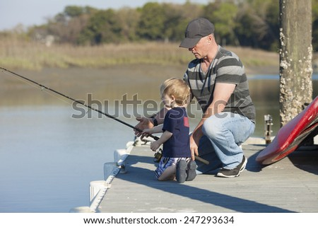 father and son fishing on dock, father gives instruction - stock photo