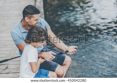 Father and son fishing. Top view of happy father and son fishing while sitting on riverbank - stock photo