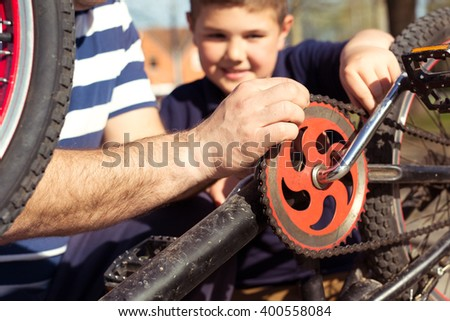 Father and son fixing bike - stock photo