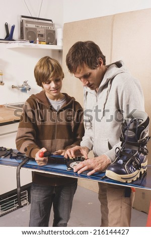 Father and son fixing snowboard