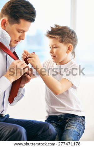 Father and son getting dressed - stock photo