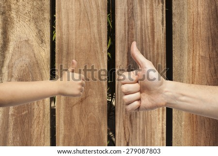 father and son hands giving like on wooden wall background.