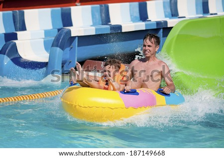 Father and son has into pool after going down water slide during summer  - stock photo