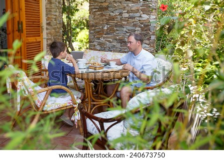 Father and son having breakfast together outdoors - stock photo