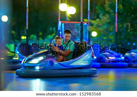 father and son having fun, driving electric toy car - stock photo