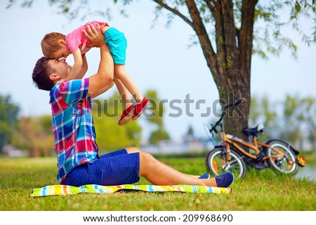 father and son having fun in city park - stock photo