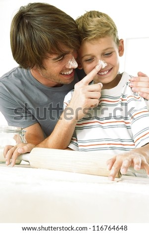 Father and son having fun in the kitchen as they dab flour on each others noses while rolling out the pastry - stock photo