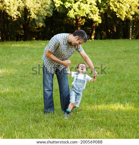 Father and son having fun in the nature - stock photo