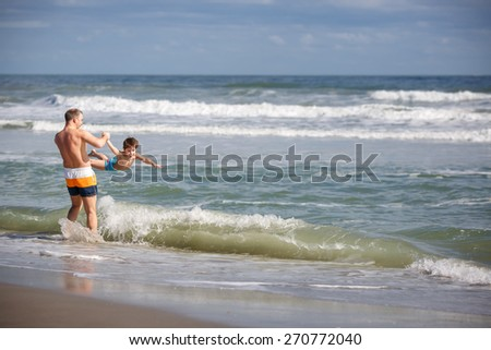 Father and son having fun on a tropical beach, Florida summer holiday vacation