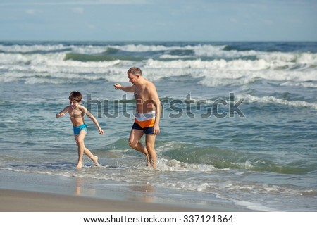 Father and son having fun on a tropical beach, Florida summer holiday vacation - stock photo