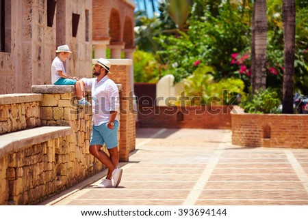 father and son having fun on cute tropical street - stock photo
