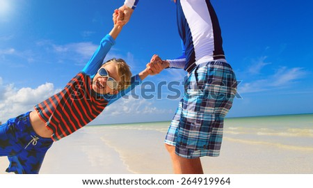father and son having fun on summer beach - stock photo
