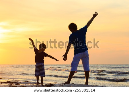 father and son having fun on sunset beach