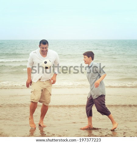 Father and son having fun on the beach and playing with a football