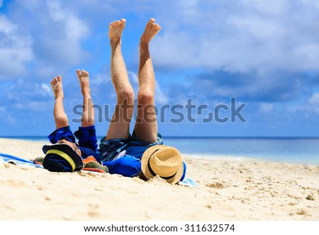 father and son having fun on the beach, family vacation - stock photo