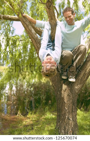 Father and son having fun on tree - stock photo