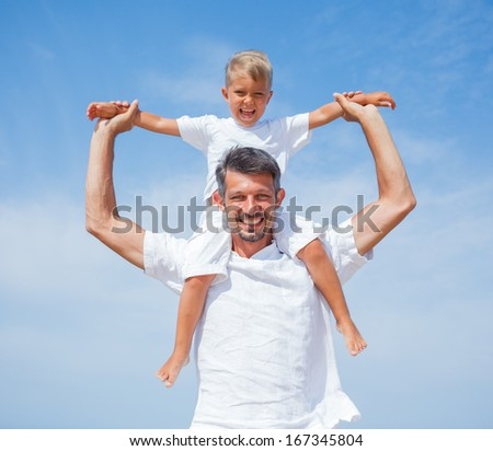 Father and son having fun on tropical beach - stock photo
