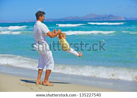 Father and son having fun on tropical white sand beach - stock photo