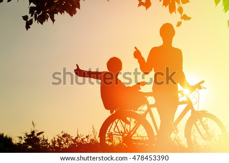 father and son having fun riding bike at sunset
