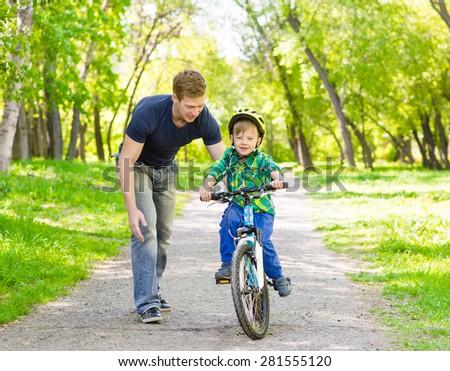 father and son having fun weekend biking - stock photo