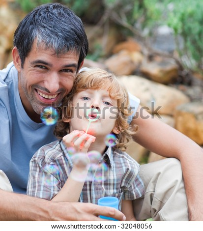 Father and son having fun with bubbles in a tent - stock photo