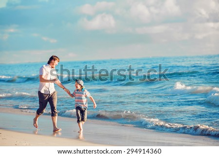 Father and son having great family time at ocean shore on summer holidays before sunset - stock photo