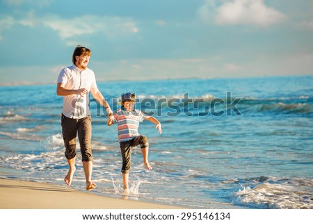 Father and son having great family time at ocean shore on summer holidays before sunset