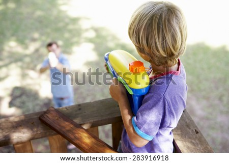 Father And Son Having Water Pistol Fight In Tree House - stock photo