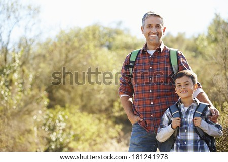 Father And Son Hiking In Countryside Wearing Backpacks - stock photo