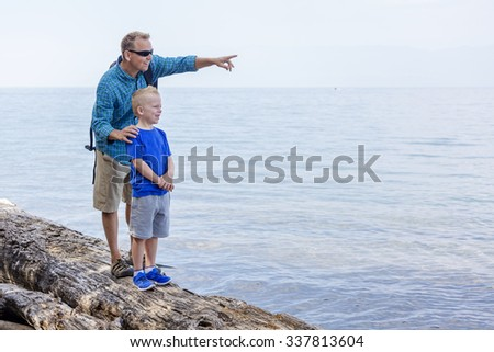 Father and son hiking together along a scenic lake. Lots of copy space and full length photo - stock photo