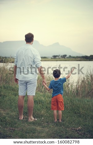 Father and son holding hands looking out over the lake at the mountain at sunset - stock photo