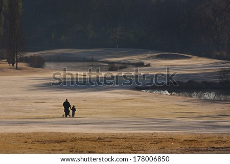 Father and son holding hands on a cold, frosty, winter morning on the golf course - stock photo