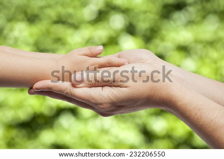 Father and son, holding hands on nature background.