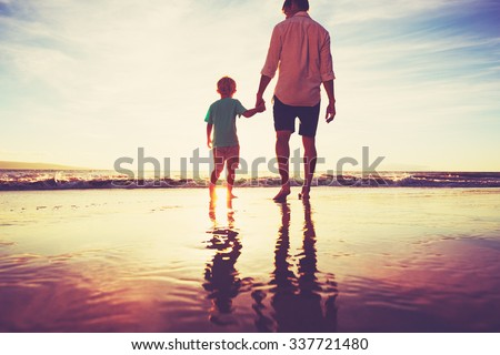 Father and Son Holding Hands Walking Together on the Beach at Sunset - stock photo