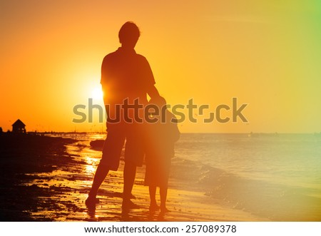 father and son hug at sunset beach - stock photo