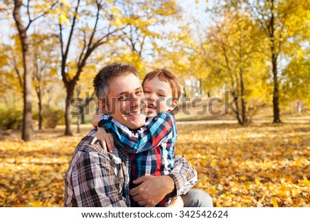 Father and son hugging in autumn park, shallow depth of field - stock photo