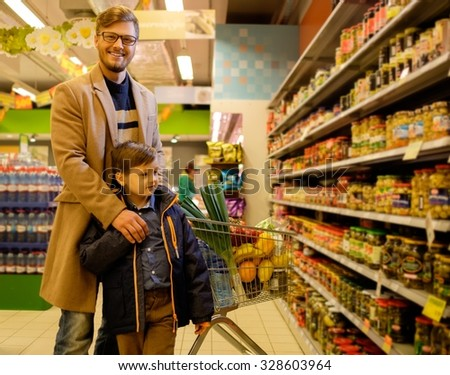 Father and son in a grocery store - stock photo