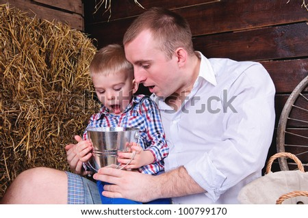 father and son, in a shed on straw. in the hands of a small bucket. People are surprised emotionally