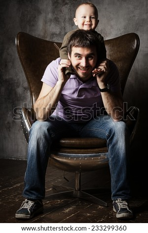 Father and son in an armchair - stock photo