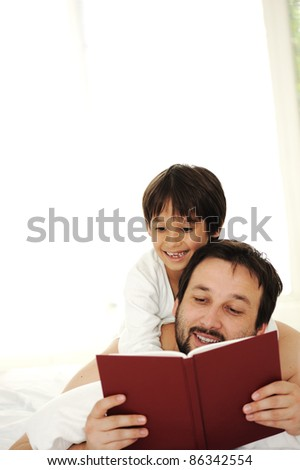 Father and son in bed, reading book together - stock photo